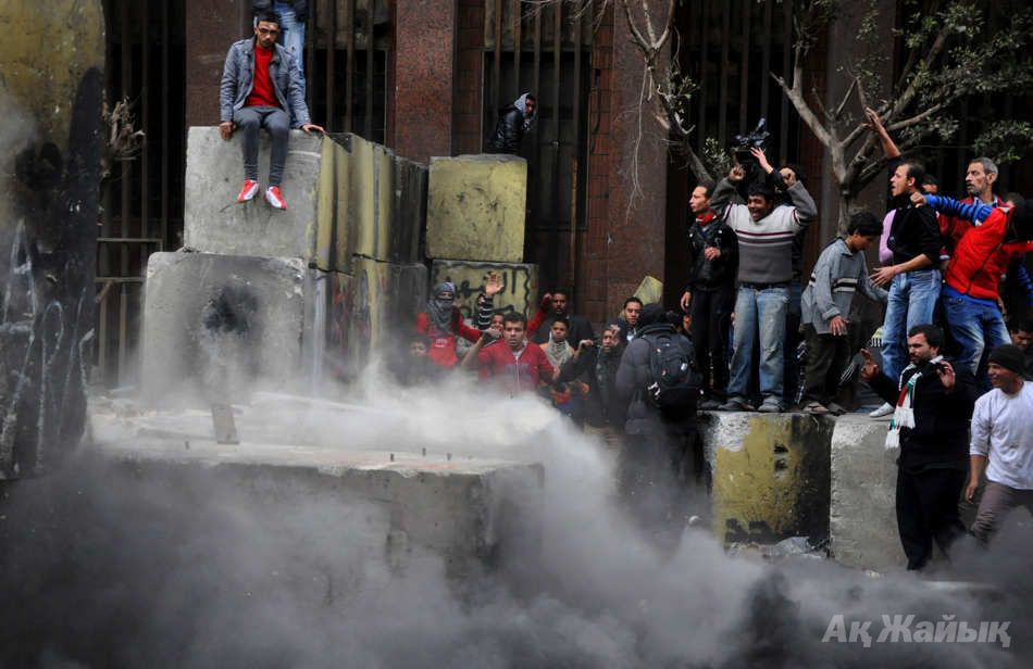 Egyptian protesters tear down a cement wall built to prevent them from reaching parliament and the Cabinet building near Tahrir Square, in Cairo, Egypt, Thursday, Jan. 24, 2013. Egypt's black-clad riot police fired tear gas in fierce dawn clashes with dozens of protesters. The violence which was soothed hours later in central Cairo comes on eve of the second anniversary of Egypt's Jan. 25 uprising, which toppled longtime authoritarian president Hosni Mubarak in 2011. (AP Photo/Hussein Tallal)