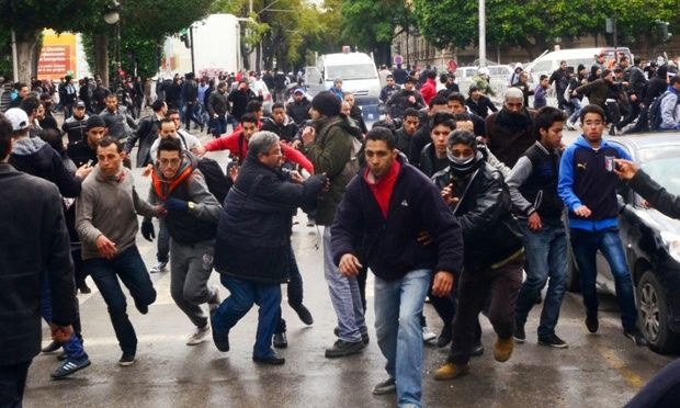 Protesters scramble in the streets of Tunis yesterday during nationwide protests at the assassination of opposition Popular Front leader Chokri Belaid.