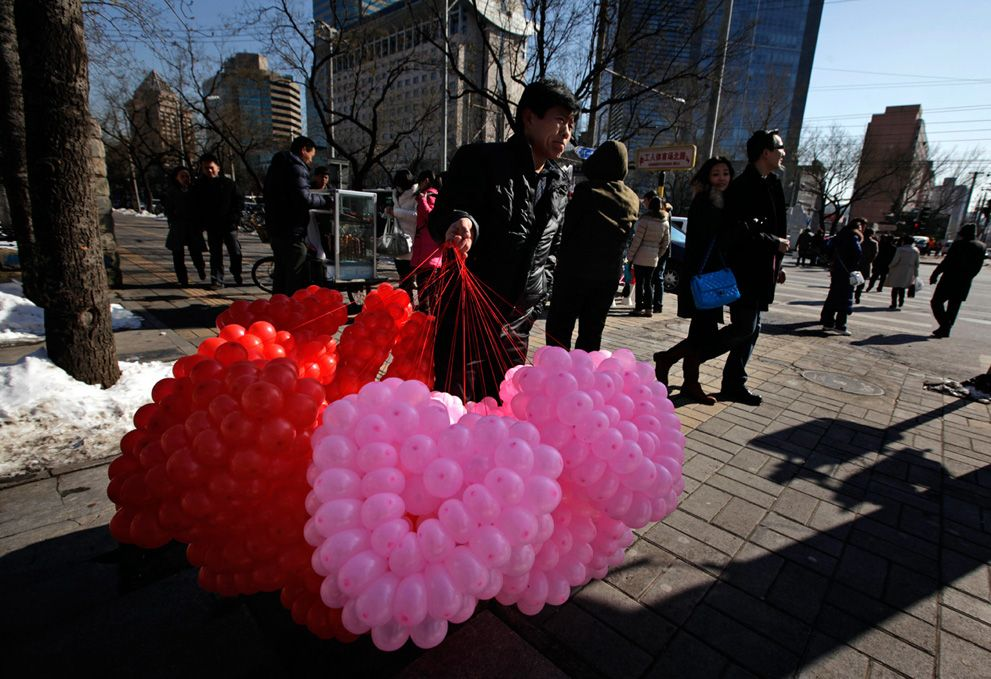 A vendor sells balloons tied in the shape of a heart for Valentine's Day in Beijing.