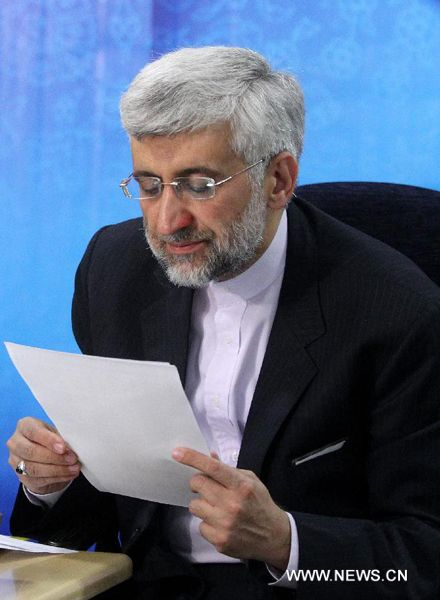 Iran's chief nuclear negotiator Saeed Jalili checks his documents as he registers his candidacy for Iran's 11th presidential election at the Interior Ministry in Tehran on May 11, 2013