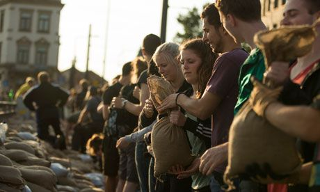 Volunteers in Dresden pass sandbags to build an embankment against the rising Elbe. Photograph: Thomas Peter/Reuters