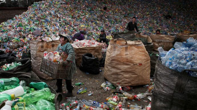 Workers sort waste plastic bottles at the Xiejiacun waste collection market in the Changping district of Beijing.(Reuters / China Daily)