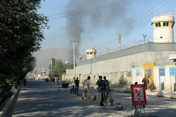 Afghan security forces stood guard as smoke rose from the entrance gate of the presidential palace in Kabul on Tuesday.