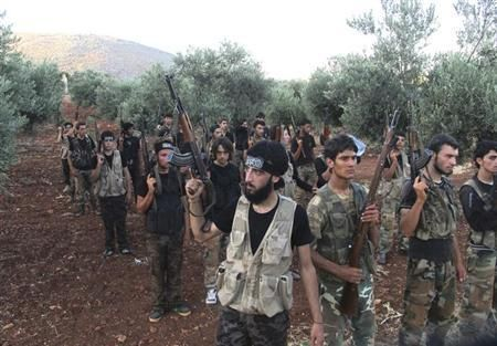 Free Syrian Army fighters, holding their weapons, stand during military training north of Idlib July 7, 2013. Picture taken July 7, 2013.