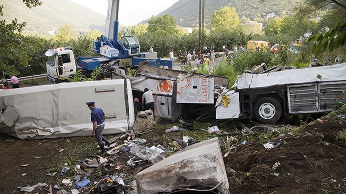 Police inspect remains of a bus crash on July 29, 2013 on the road between Monteforte Irpino and Baiano, southern Italy. (AFP Photo / Carlo Hermann)