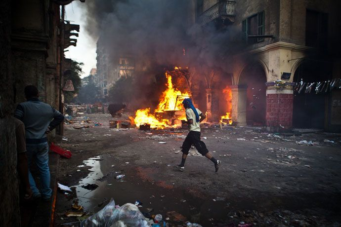 A supporter of the Muslim Brotherhood and of ousted president Mohamed Morsi runs past a burning vehicle during clashes with security officers close to Cairo's Ramses Square, on August 16, 2013.(AFP Photo / Virgnie Nguyen Hoang)