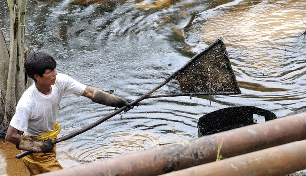 An employee of state-owned Petroecuador works on a cleaning operation of a 30-year old oil spill at the Rumipamba commune, 200 mt form the Auca Sur 1 oil well --operated by Chevron Texaco in the seventies-- in the province of Orellana, Amazonia, on Feb. 20, 2011. Photograph by Rodrigo Buendia/AFP via Getty Images