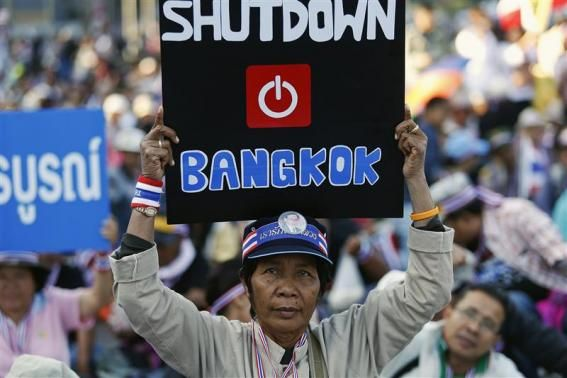 An anti-government protester joins others blocking the road at one of major intersections in central Bangkok January 13, 2014.