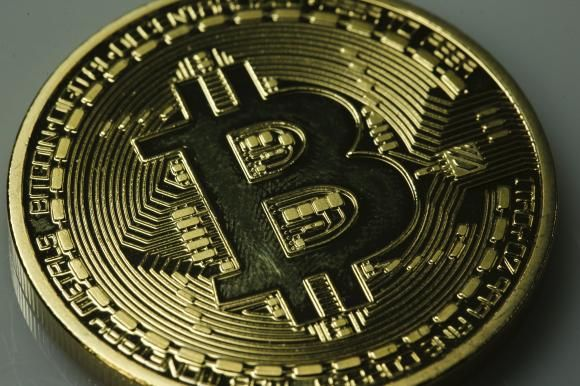 A mock Bitcoin is displayed on a table in an illustration picture taken in Berlin January 7, 2014.
