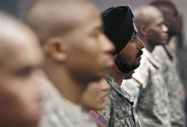 U.S. Army Spc. Simran Lamba, center, the first enlisted Soldier to be granted a religious accommodation for his Sikh articles of faith since 1984, stands in formation with fellow soldiers before taking the oath of citizenship, prior to his graduation from basic training at Fort Jackson, S.C