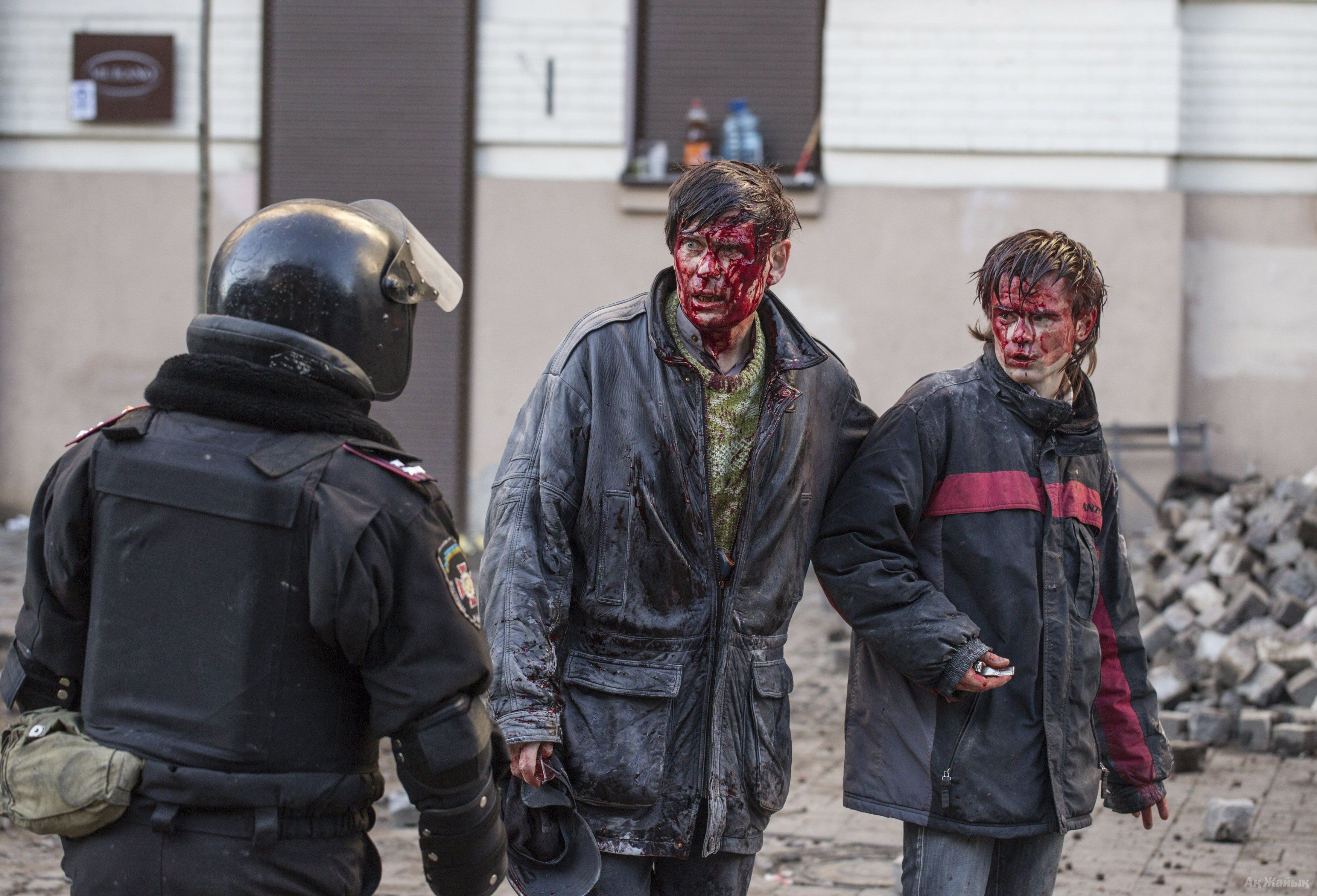 Wounded people are seen after clashes with riot police in central Kiev February 18, 2014.