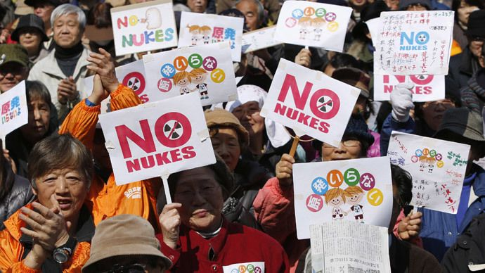 Anti-nuclear protesters hold banners saying