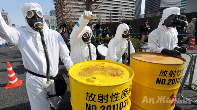 People wearing protective suits and masks shout slogans next to mock drums of nuclear waste from the Fukushima Daiichi nuclear power plant, during a march denouncing nuclear power plants in Tokyo on March 9, 2014. (AFP Photo