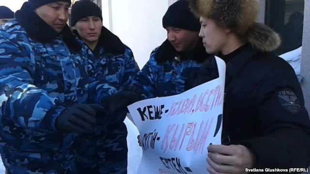 Kazakh police speak with Makhambet Abzhan (right) outside the Russian Embassy in Astana on March 3.