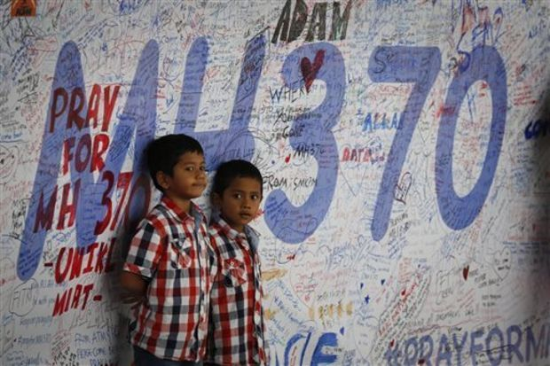 wo Malaysian children stand in front of a message board offering prayers to those aboard the missing plane. (Associated Press)