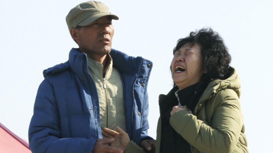April 21, 2014: A relative of a passenger aboard the sunken ferry Sewol shouts the name of her missing family member as she waits for their return at a port in Jindo, South Korea. (AP Photo)