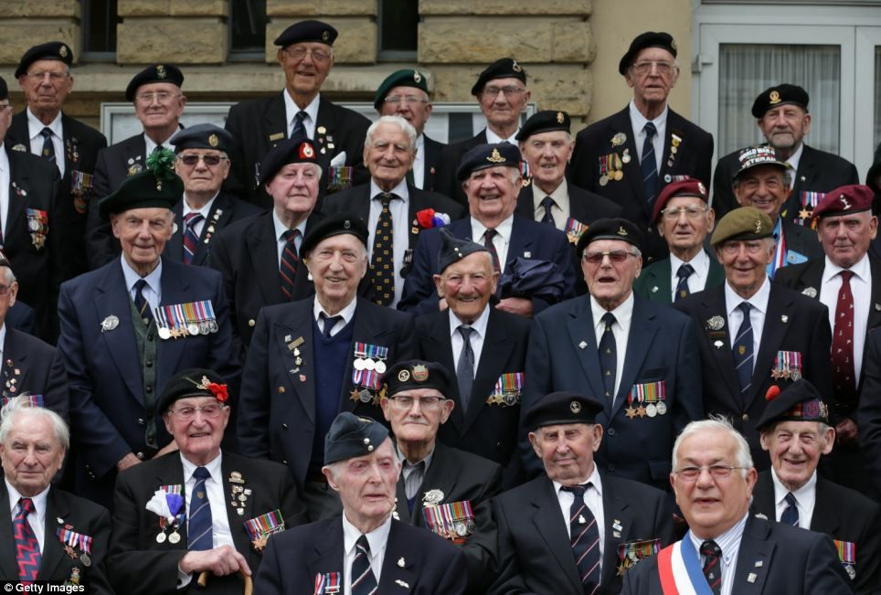 A group of veterans gather for a photograph with the local mayor at a civic function in the village of Thury-Harcourt near Caen during their action packed day  Read more: http://www.dailymail.co.uk/news/article-2648320/D-Day-veterans-embark-ferry-journey-ahead-70th-anniversary-celebrations-invasion-Europe.html#ixzz33m1p9a00  Follow us: @MailOnline on Twitter | DailyMail on Facebook