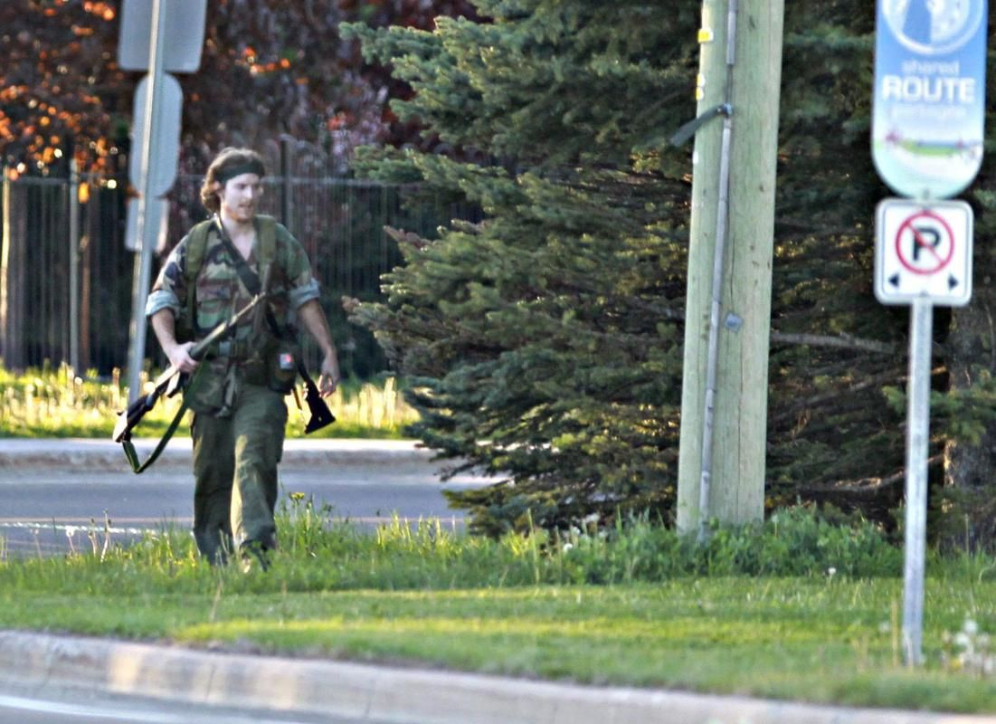 A heavily armed man that police have identified as Justin Bourque walks on Hildegard Drive in Moncton, New Brunswick, on Wednesday, June 4, 2014.
