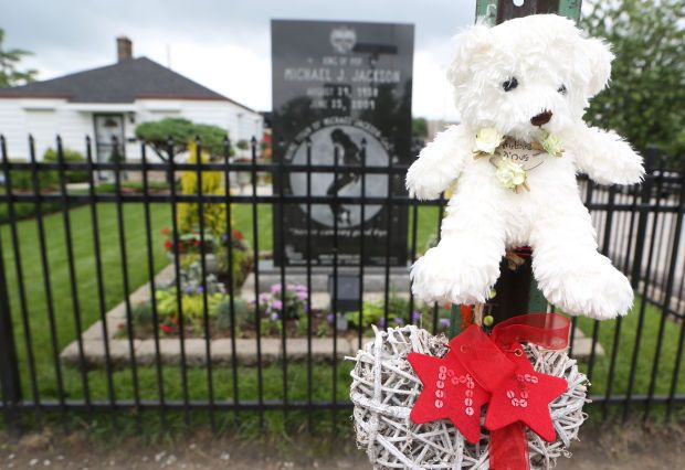 A stuffed bear and a heart decoration adorn a sign posted outside Michael Jackson's childhood home at 2300 Jackson St. in Gary on Tuesday, the day before the fifth anniversary of his death.