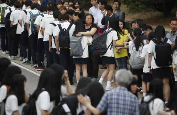 Relatives of the April 16 ferry disaster victims comfort students who survived the accident as they make their way back to school in Ansan June 25, 2014.