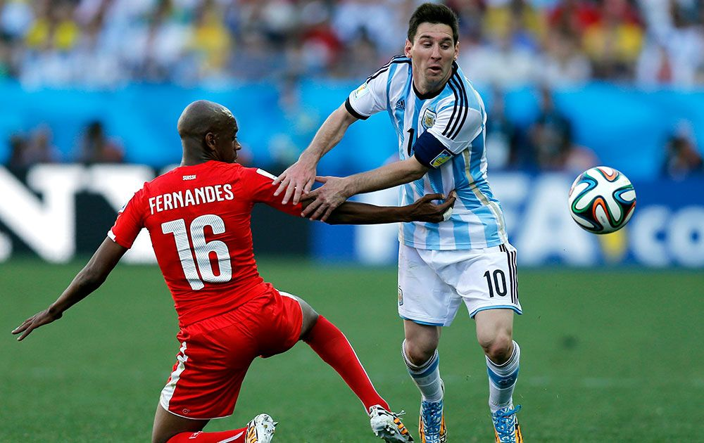 Switzerland's Gelson Fernandes, left, tries to stop Argentina's Lionel Messi during the World Cup round of 16 soccer match between Argentina and Switzerland at the Itaquerao Stadium in Sao Paulo, Brazil.