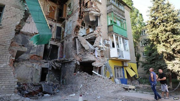 Men look at a building destroyed by the Ukrainian Air Force in Snezhnoye, 80 km east of Donetsk, on July 16 Cities across the east have sustained severe damage