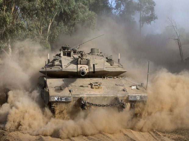 An Israeli Merkava tank rolls near Israel's border with the Gaza Strip Thursday.