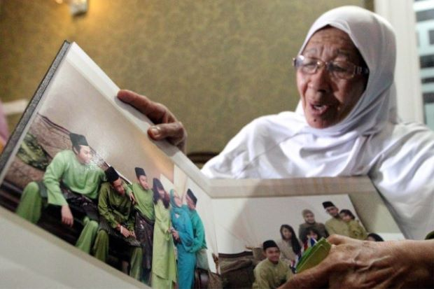 Jamillah showing the family photo album at her home. Pix by Zulazhar Sheblee/The Star