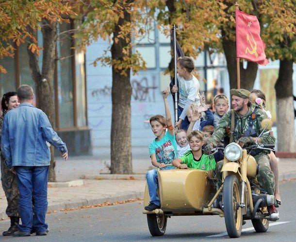 Children ride the motorcycle of an armed pro-Russian militant in the eastern Ukrainian city of Lugansk on September 14, 2014 during the celebration of the day of the city.