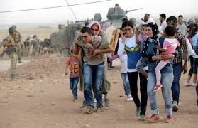 Syrian Kurds walk after crossing into Turkey at the Turkish-Syrian border, near the southeastern town of Suruc in Sanliurfa province, September 20, 2014