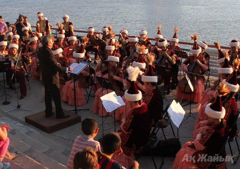 Dina Nurpeissova folk orchestra performing on the bank of the Ural River on July 6, 2014.