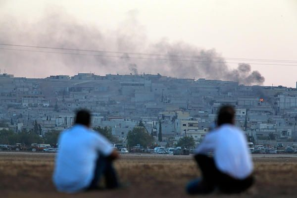 Turkish Kurds sit on the outskirts of Suruc, on the Turkey-Syria border, as they watch smoke rising from a fire following an airstrike in Kobane, Syria, where the fighting between militants of the Islamic State group and Kurdish forces intensified, Tuesday, Oct. 7, 2014.