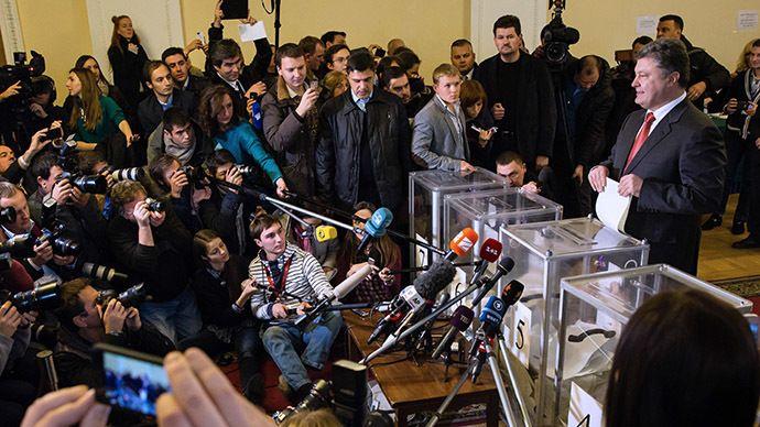 Ukrainian President Petro Poroshenko holds ballots at a polling station in Kiev (RIA Novosti)