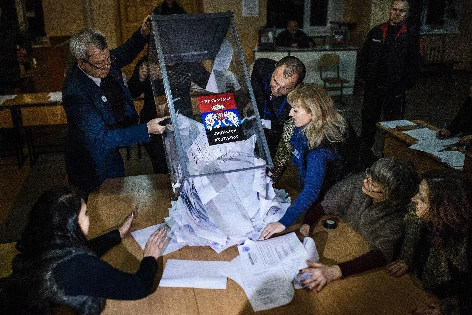 Electoral workers empty a ballot box to start counting ballots for the leadership vote