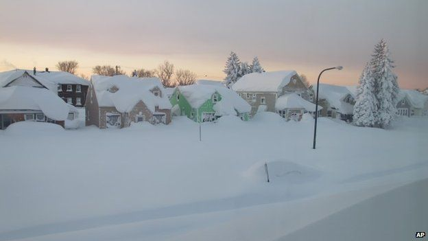 Snow covers a street at daybreak in Buffalo