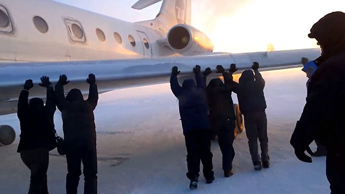 Passengers pushing the plane with its wheels frozen (Screenshot from youtube.com)