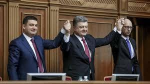 Ukrainian President Petro Poroshenko (center) congratulates the newly elected Ukrainian Prime Minister Arseniy Yatsenyuk (right) and parliament speaker Volodymyr Hroysman during a session of the Verkhovna Rada in Kyiv on November 27.