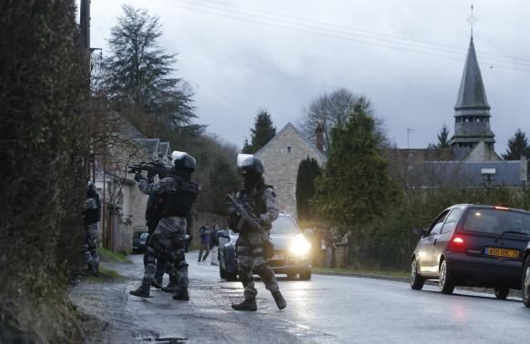 Members of the French GIPN intervention police forces secure a neighbourhood in Corcy, northeast of Paris January 8, 2015.