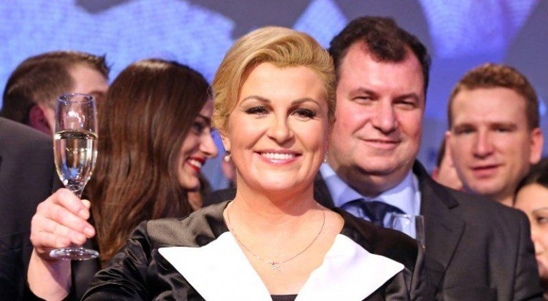 The presidential candidate Kolinda Grabar-Kitarovic (C), toasts as she celebrates after hearing the first results of the Croatian presidential elections. ©AFP