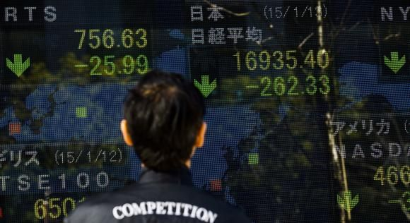 A man looks at an electronic board displaying Japan's Nikkei average (top R) in Tokyo January 13, 2015.