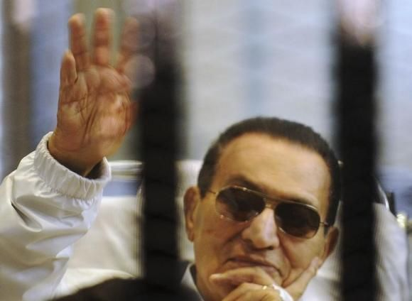 Former Egyptian President Hosni Mubarak waves to his supporters inside a cage in a courtroom at the police academy in Cairo April 13, 2013.