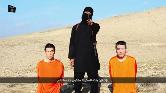 A masked person holding a knife speaks as he stands in between two kneeling men in this still image taken from an online video released by the militant Islamic State group on January 20, 2015. Reuters