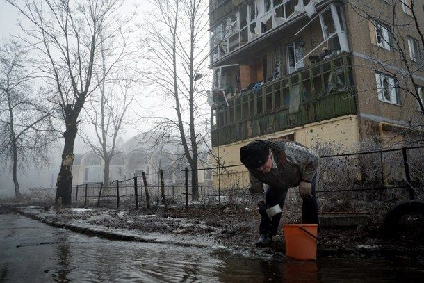 A resident collects water from a broken pipe in the eastern Ukrainian city of Donetsk on Feb. 15. Fighting dropped sharply but there was still sporadic shooting after a ceasefire came into force across east Ukraine, the first step in a fragile peace plan aimed at ending 10 months of conflict.