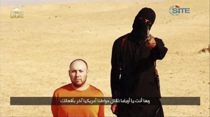 A masked, black-clad militant, who has been identified by the Washington Post newspaper as a Briton named Mohammed Emwazi, stands next to a man purported to be Steven Sotloff in this still image from video.