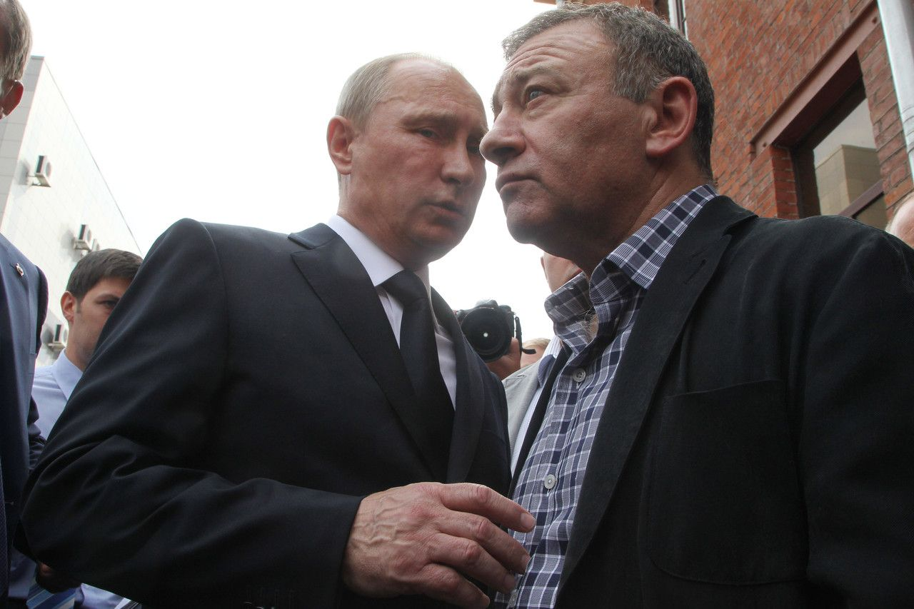 Russian President Vladimir Putin, left, and billionaire Arkady Rotenberg attend the funeral of a former judo trainer in St. Petersburg in 2013. PHOTO: GETTY IMAGES