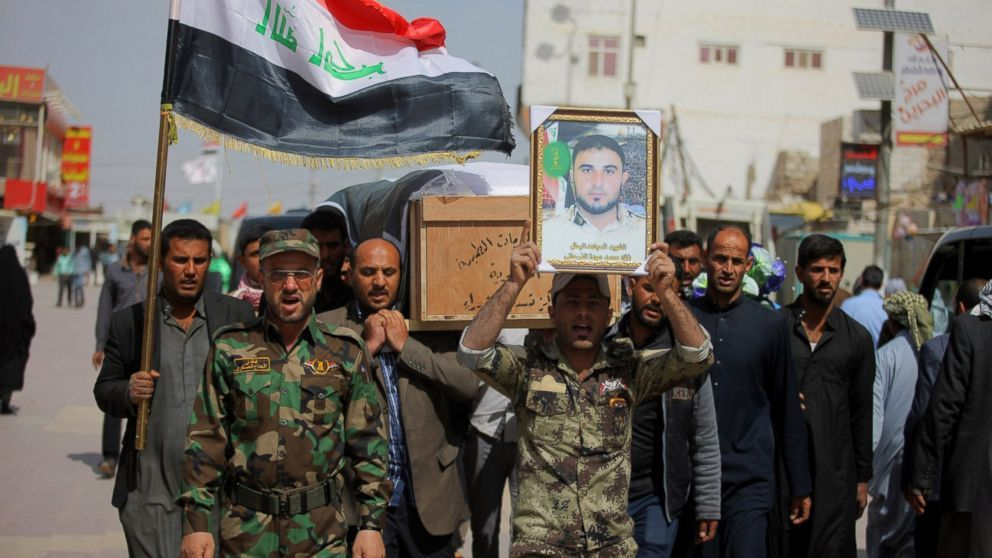 Members of the Iraqi Shiite militant group Badr Brigades carry the coffin of Mohammed Fuad and a poster with his picture during his funeral procession in Najaf, Iraq, Monday, March 9, 2015. Iraqi security forces on Tuesday retook a town next to the militant-held city of Tikrit as they pressed their offensive against Islamic State militants.