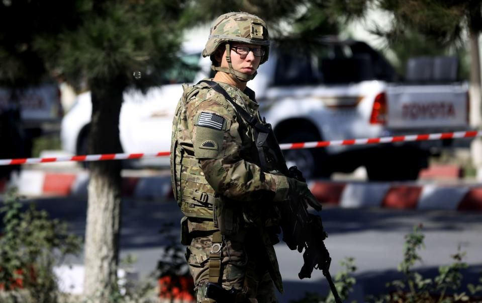 In this Sept. 16, 2014, file photo, a U.S. solider stands guard at the site of a suicide attack near a U.S. military camp in Kabul, Afghanistan.