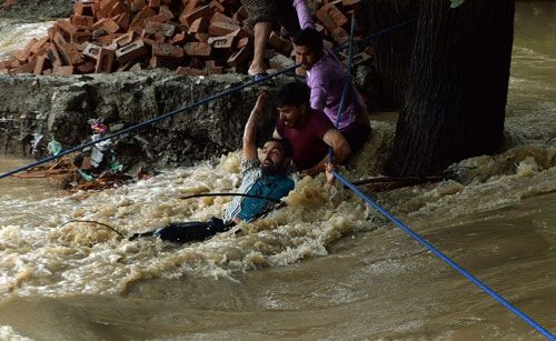A man being rescued from teh storm. AFP PHOTO