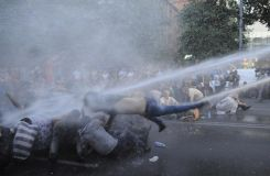 Protesters are hit by a jet of water in Yerevan, Armenia, June 23, 2015.